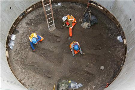Archaeologists work on unearthed skeletons in the Farringdon area of London in this undated handout photograph released March 15, 2013. Archaeologists said on Friday they had found a graveyard during excavations for a rail project in London which might hold the remains of some 50,000 people killed by the ''Black Death'' plague more than 650 years ago. Thirteen skeletons laid out in two neat rows were discovered 2.5 metres (8 feet) below the road in the Farringdon area of central London by researchers working on the 16 billion pound ($24 billion) Crossrail project. REUTERS/Crossrail/Handout
