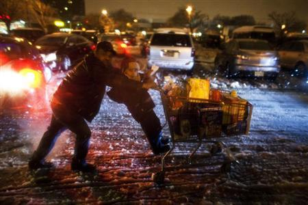 A child hangs on to shopping cart as his father pushes as they make their way to their car during a winter storm at Jersey City in New Jersey, February 8, 2013. REUTERS/Eduardo Munoz
