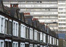 A terraced row of houses is pictured in front of a residential tower block in London January 16, 2009. REUTERS/Luke MacGregor (BRITAIN) - RTR23WBO
