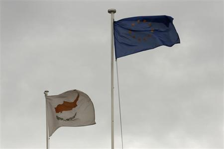 European Union (EU) and Cypriot flags flutter atop the Presidential palace in Nicosia February 22, 2013. REUTERS/Yorgos Karahalis