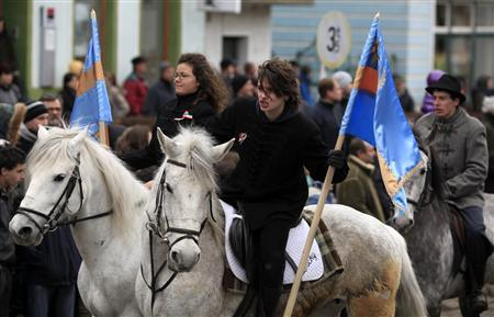 Two ethnic Hungarian women hold the Szekler flag, the symbol of the Hungarian minority living in Romania, as they parade on horses during a Magyar's Day ceremony in Targu Secuiesc, 280km (174 miles) north of Bucharest March 15, 2013. REUTERS/Radu Sigheti