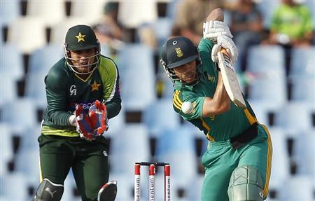 Pakistan's wicket keeper Kamran Akmal (L) looks on as South Africa's Farhaan Behardien (R) plays a shot during their second One Day International (ODI) cricket match in Centurion, March 15, 2013. REUTERS/Siphiwe Sibeko