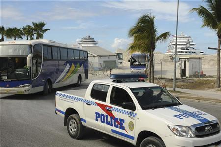 A police car escorts buses carrying passengers of the Carnival Dream cruise ship, as they leave towards the international airport for flights back to the U.S. after their cruise was cancelled, at the A.C. Wathey Cruise Facilities port in Philipsburg, Sint Maarten, March 15, 2013. REUTERS/John Halley