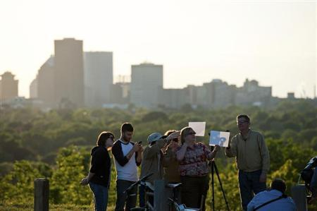 People watch from Cobbs Hill Reservoir as the planet Venus transits across the sun over Rochester, New York, June 5, 2012. REUTERS/Adam Fenster