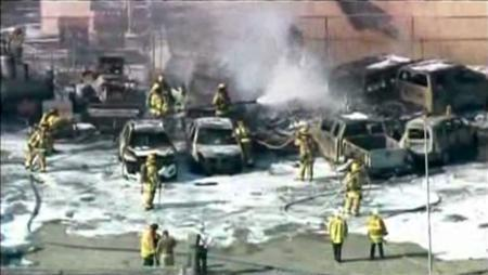 Firefighters hose down the scene of a fire in this video screen capture courtesy NBC6, after a small twin-engine plane crashed into parked vehicles and burned shortly after takeoff from Fort Lauderdale Executive Airport in Fort Lauderdale, Florida March 15, 2013. Three people are reported killed in the incident. REUTERS/NBC6-TV/Handout