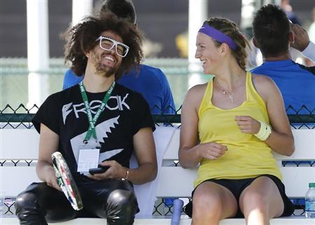 Victoria Azarenka of Belarus (R) laughs with her boyfriend singer Redfoo, also known as Stefan Gordy of the band LMFAO, during a practice session as she prepares for the BNP Paribas Open WTA tennis tournament in Indian Wells, California, March 6, 2013. REUTERS/Danny Moloshok