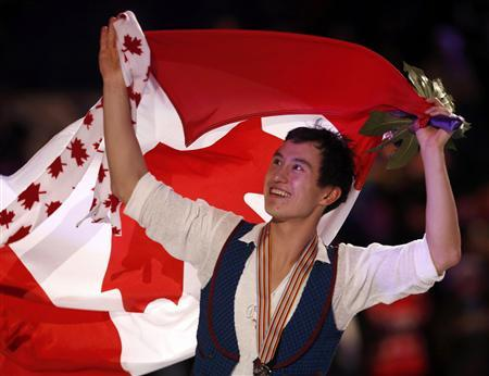 Patrick Chan of Canada carries his country's flag as he celebrates his gold medal finish after the presentation ceremony at the ISU World Figure Skating Championships in London, March 15, 2013. REUTERS/Mark Blinch