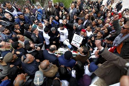 Basma, the widow, and the family of assassinated secular opposition leader Chokri Belaid, gather at his tomb to mark the 40th day of mourning after his death in Tunis March 16, 2013. REUTERS/Anis Mili