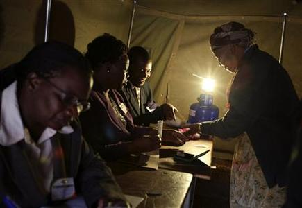 A woman is helped by officials as she votes in a referendum at a polling station in Harare March 16, 2013. REUTERS/Philimon Bulawayo
