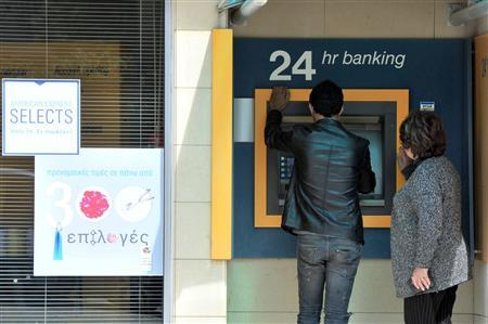 People gather at an automatic teller machine in Nicosia March 16, 2013. REUTERS-Yiannis Nisiotis