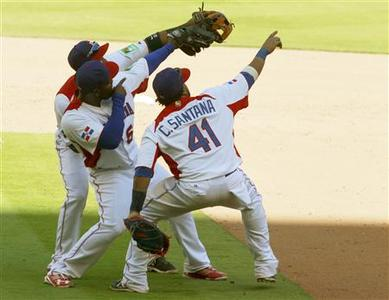 Dominican Republic players (L-R) Robinson Cano, Fernando Rodney and Carlos Santana celebrate after their team defeated Puerto Rico during a 2013 World Baseball Classic game in Miami, Florida March 16, 2013. REUTERS/Joe Skipper