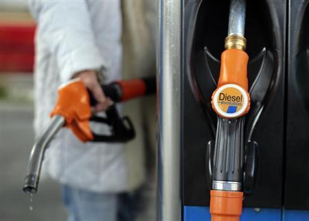 A customer holds a gas pump as he fills-up his car with diesel at a station in Nice March 4, 2013. REUTERS/Eric Gaillard
