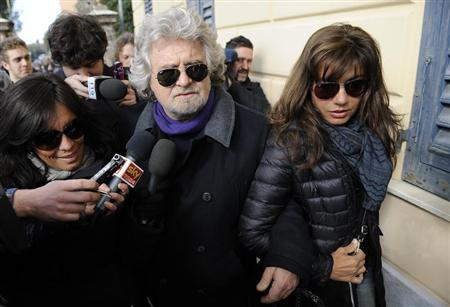 Five Star Movement leader and comedian Beppe Grillo and his wife Parvin Tadjik arrive to cast their votes at the polling station in Genoa February 25, 2013. REUTERS/Giorgio Perottino