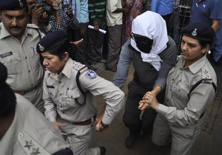 A Swiss woman with her face covered is taken to a hospital by police for her medical examination at Gwalior in Madhya Pradesh March 16, 2013. REUTERS/Stringer