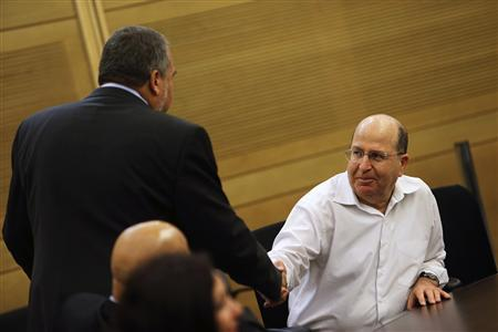 Moshe Yaalon (R) shakes hands with Israel's former foreign minister Avigdor Lieberman during a Likud-Beiteinu party meeting at the Knesset, the Israeli parliament, in Jerusalem March 14, 2013. REUTERS/Nir Elias