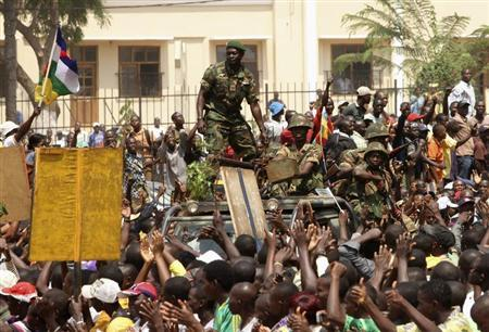 Supporters of Central African Republic's President Francois Bozize cheer for soldiers as they follow the presidential convoy heading for the airport in Bangui January 10, 2013. REUTERS/Luc Gnago