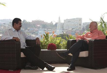 Venezuela's acting President Nicolas Maduro (L) speaks during an interview in Caracas, March 16, 2013, in this handout photo provided by the Miraflores Palace. REUTERS/Miraflores Palace/Handout