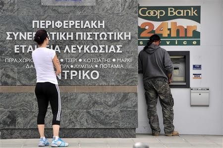People gather at an automatic teller machine in Nicosia March 16, 2013. REUTERS/Yiannis Nisiotis