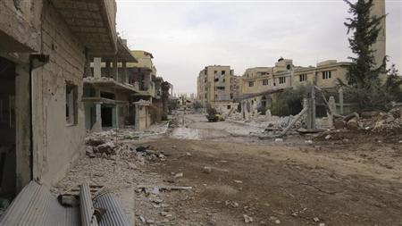 A view shows damaged buildings and a vehicle on a deserted street in Deraa February 22, 2013. Picture taken February 22, 2013. REUTERS/Ali Abu Salah/Shaam News Network/Handout