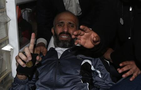 Freed Palestinian prisoner Ayman Sharawneh gestures as he holds a copy of the Koran inside an ambulance upon his arrival near Erez crossing in the northern Gaza Strip March 17, 2013. REUTERS/Mohammed Salem