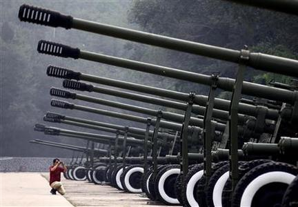 A visitor to the China Aviation Museum, located on the outskirts of Beijing, takes a photograph of a row of old anti-aircraft guns on display in this August 17, 2010 file photo. REUTERS/David Gray/Files