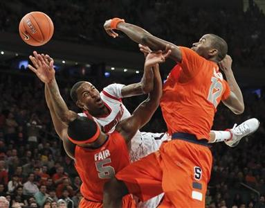 Louisville Cardinals guard Kevin Ware tries to pass the ball under pressure from Syracuse Orange forward C.J. Fair (5) and center Baye Keita (12) during the second half of their NCAA men's championship final basketball game at the 2013 Big East Tournament in New York, March 16, 2013. REUTERS/Ray Stubblebine