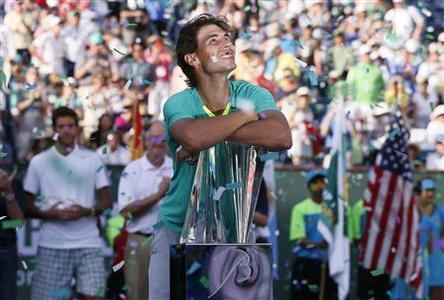 Rafael Nadal of Spain smiles as he leans on his trophy, while confetti flutters in the air, after he defeated Juan Martin Del Potro (rear L) of Argentina in the men's singles final match to win the BNP Paribas Open ATP tennis tournament in Indian Wells, California, March 17, 2013. REUTERS/Danny Moloshok