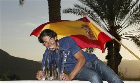 Rafael Nadal of Spain poses with his trophy and the Spanish flag after defeating Juan Martin Del Potro of Argentina in the men's singles final match to win the BNP Paribas Open ATP tennis tournament in Indian Wells, California, March 17, 2013. REUTERS/Danny Moloshok