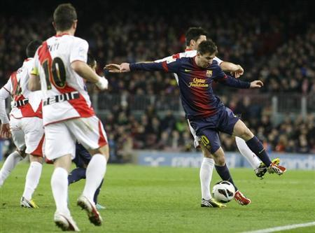 Barcelona's Lionel Messi (R) is challanged by Rayo Vallecano players during their Spanish first division soccer match at Nou Camp stadium in Barcelona March 17, 2013. REUTERS/Gustau Nacarino