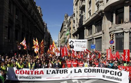 People hold banners and placards as they march during a protest against government austerity measures in Barcelona March 10, 2013. REUTERS/Albert Gea