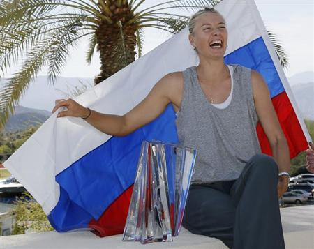 Maria Sharapova of Russia poses with her trophy and the Russian flag after defeating Caroline Wozniacki of Denmark in the women's singles final match at the BNP Paribas Open WTA tennis tournament in Indian Wells, California March 17, 2013. REUTERS/Danny Moloshok