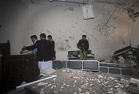 Security officials inspect the site of bomb blast in a judicial compound in Peshawar March 18, 2013. Two suicide bombers attacked a judicial compound in the Pakistani city of Peshawar on Monday, killing four people and taking hostages, officials said. REUTERS/Fayaz Aziz