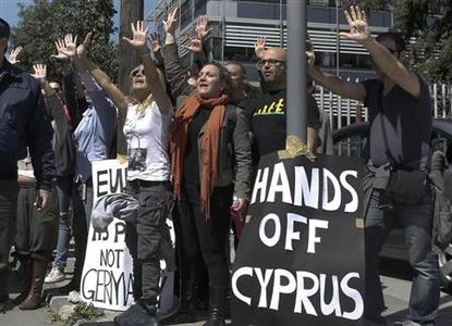 Demonstrators raise their arms in protest as Cypriot President Nicos Anastasiades's convoy drives to the parliament in Nicosia March 18, 2013. REUTERS/Yorgos Karahalis/Files