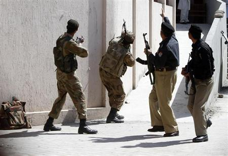 Policemen and army soldiers fan out to secure the area after a suicide bomb blast in a judicial compound in Peshawar March 18, 2013. REUTERS/Fayaz Aziz