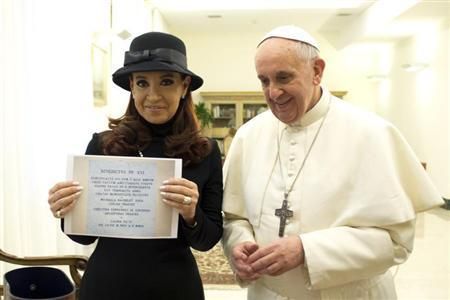 Argentine President Cristina Fernandez shows a gift as she stands next to newly elected Pope Francis during a private meeting at the Vatican March 18, 2013. REUTERS/Osservatore Romano