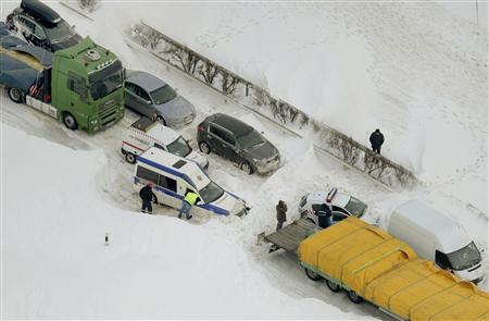 Drivers stand outside their vehicles stranded in the snow on the M1 highway, west of Budapest, in this March 16, 2013 handout picture by the ORFK (National Police Headquarters). REUTERS/Szabo H. Sandor/ORFK/Handout