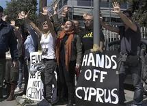 Manifestation à Nicosie, au passage du président Nicos Anastasiades, contre le projet de taxation exceptionnelle des dépôts bancaires. Le gouvernement chypriote s'efforce d'adoucir autant que possible ce projet prévu par le plan de sauvetage du pays, une disposition sans précédent en Europe qui suscite l'hostilité des Chypriotes, l'embarras de certains partenaires de Nicosie et l'inquiétude des marchés. /Photo prise le 18 mars 2013/REUTERS/Yorgos Karahalis