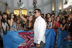 "Judge Simon Cowell poses with a fan at the season two premiere of the television series ""The X Factor"" at Grauman's Chinese theatre in Hollywood, California September 11, 2012. REUTERS/Mario Anzuoni"