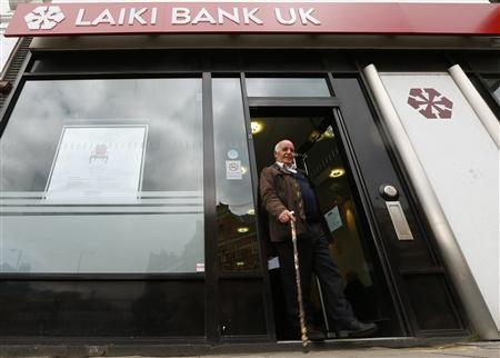 A customer walks out of a branch of Laiki Bank UK, in north London March 18, 2013. REUTERS/Andrew Winning