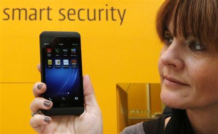 A woman poses with a BlackBerry Z10 smartphone featuring high security Secusite software, used for governmental communication, at the booth of Secusmart during preparations at the CeBit computer fair in Hanover, March, 4, 2013. REUTERS/Fabrizio Bensch