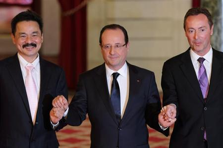 Fabrice Bregier (R), Airbus President and Chief Executive Officer, Rusdi Kirana (L), Lion Air Chief Executive Officer, and French President Francois Hollande (C) pose after a signing ceremony at the Elysee Palace in Paris, March 18, 2013. REUTERS/Philippe Wojazer