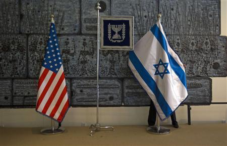 An employee arranges an Israeli national flag next to a U.S. one at the residence of Israel's President Shimon Peres in Jerusalem, ahead of U.S. President Barack Obama's visit, March 18, 2013. REUTERS/Ronen Zvulun