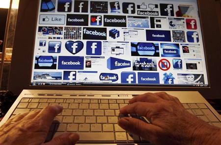 A women works with her computer which displays Facebook logos on the screen in Bordeaux, Southwestern France, January 30, 2013. REUTERS/Regis Duvignau/Files