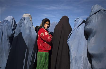 An Afghan girl stands among widows clad in burqas during a cash for work project by humanitarian organisation CARE International in Kabul January 6, 2010. REUTERS/Ahmad Masood
