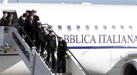 Italian marines Salvatore Girone (2nd L from centre) and Massimiliano Latorre (centre L) alight from the plane with Italian Navy Chief of Staff Admiral Luigi Pinelli Mantelli (C) after landing at Ciampino airport in Rome, December 22, 2012. REUTERS/Alessandro Bianchi