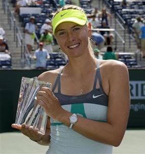 Maria Sharapova of Russia poses with a smaller replica trophy after defeating Caroline Wozniacki of Denmark in their women's singles final match at the BNP Paribas Open WTA tennis tournament in Indian Wells, California March 17, 2013. REUTERS/Danny Moloshok