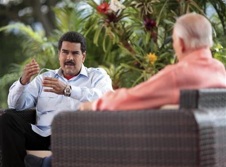 Venezuela's acting President Nicolas Maduro (L) speaks during an interview in Caracas, March 16, 2013, in this handout photo provided by the Miraflores Palace. Picture taken on March 16, 2013. REUTERS/Miraflores Palace/Handout