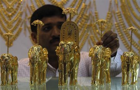 An employee displays gold models of elephants at the ''Gem and Jewellery India International Exhibition 2013'' (GJIIE) in Chennai March 17, 2013. REUTERS/Babu