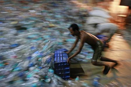 A man collects empty plastic bottles to be recycled at a factory in a slum in Mumbai March 15, 2013. REUTERS/Danish Siddiqui