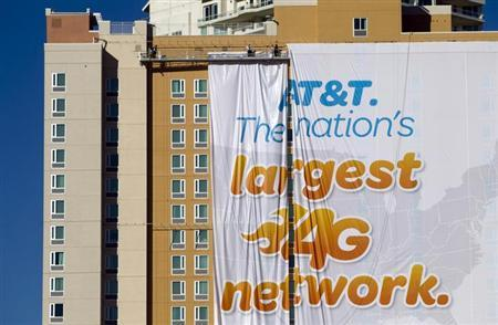 Workers put up a banner advertisement for AT&T on the side of a hotel as they prepare for International CES show in Las Vegas, Nevada January 4, 2013. REUTERS/Steve Marcus